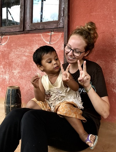 Global Service Scholar Jordan Stead spends time with a child in Nepal in 2018.